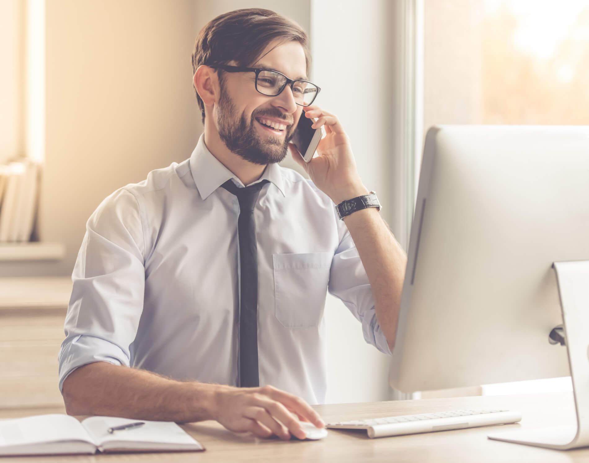 mężczyzna rozmawia przez telefon przy biurku