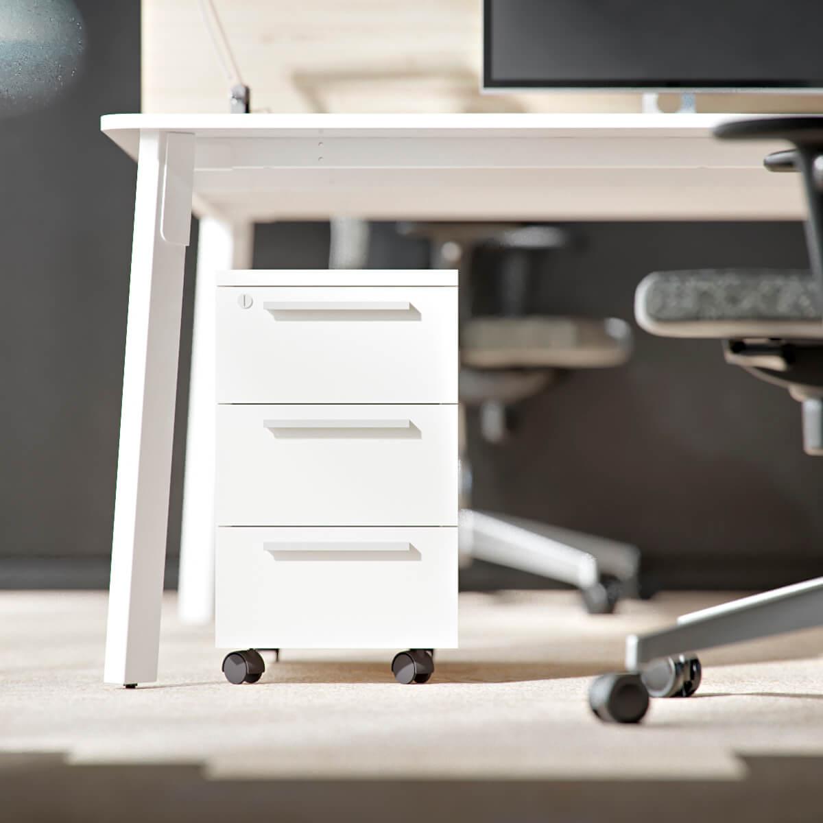 biały kontenerek stoi pod biurkiem