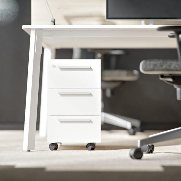biały kontenerek wąski stoi pod biurkiem