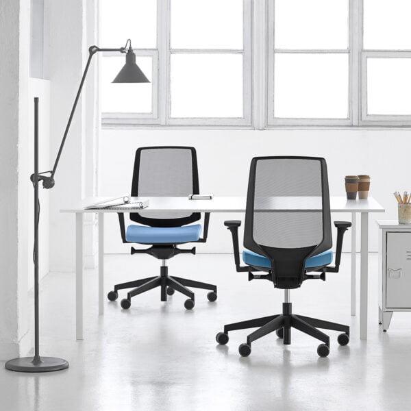 dwa fotele niebieskie przy biurkach