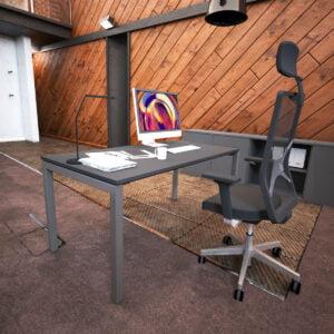 grafitowe biurko i czarny fotel biurowy, w tle drewniana ściana
