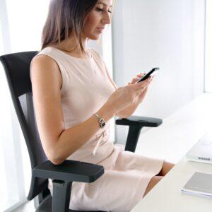 atrakcyjna pani sprawdza pisze sms siedząc w biurze