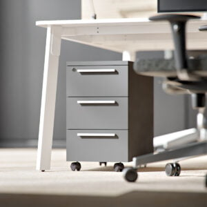 wąski grafitowy kontenerek stoi pod biurkiem
